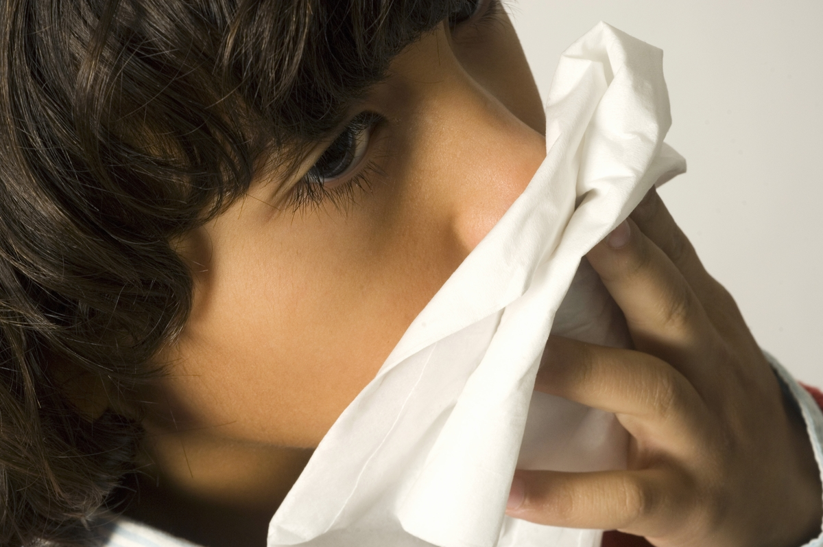 Close-up of boy blowing nose