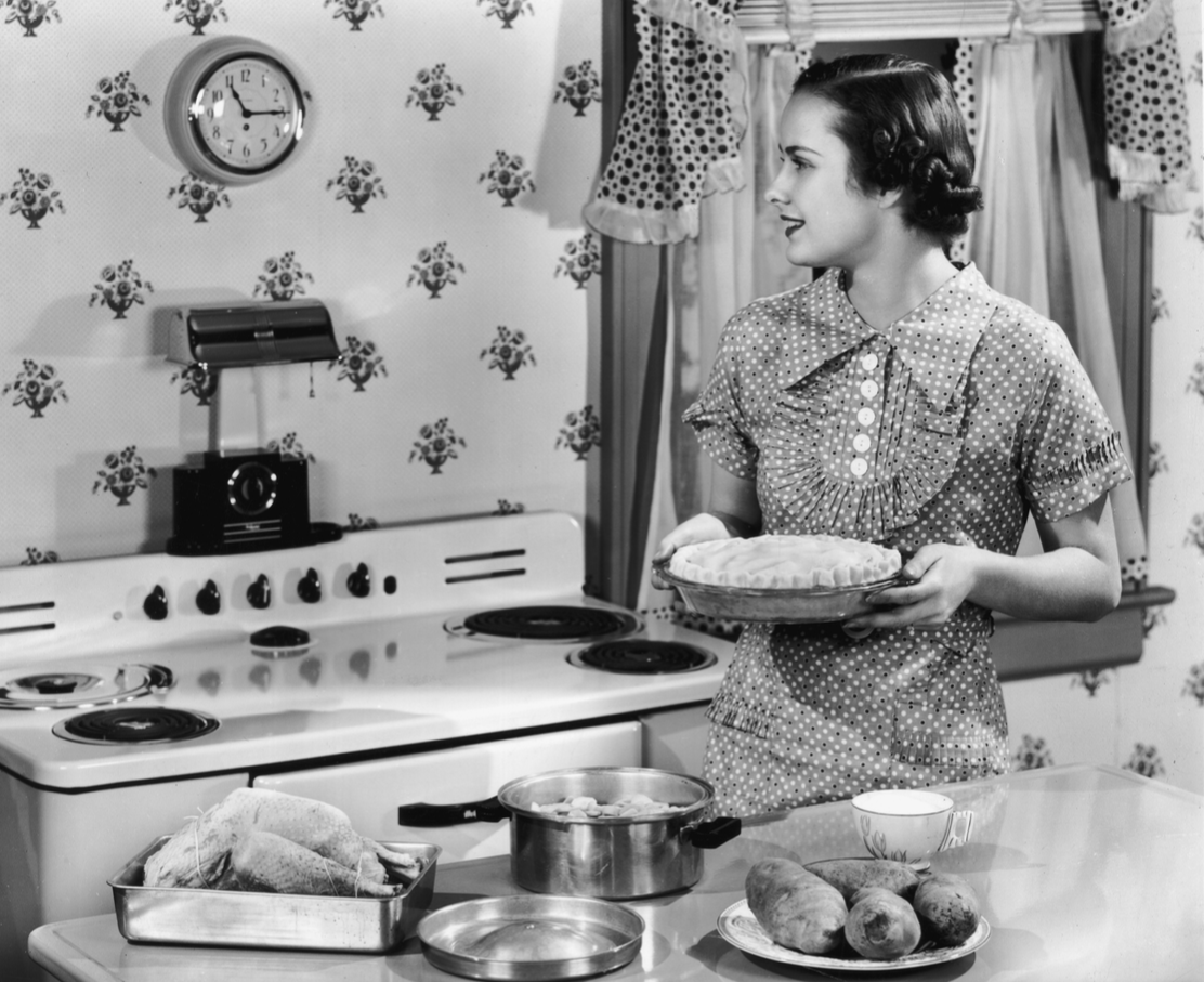 A woman holds an unbaked pie while looking at a wall clock in a kitchen.