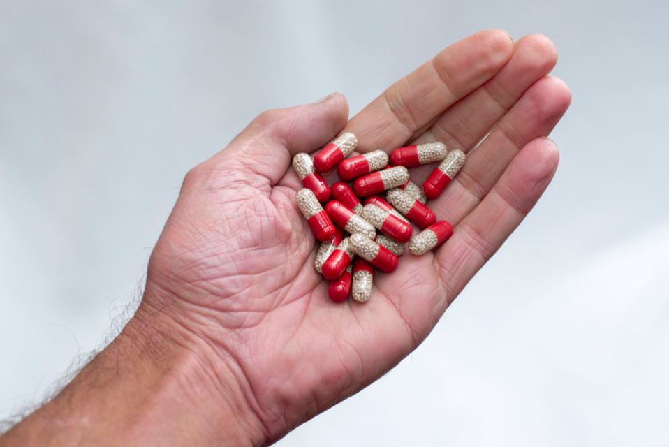 Many red and transparent medical capsules, filled with yellow medicine, displayed on a hand.