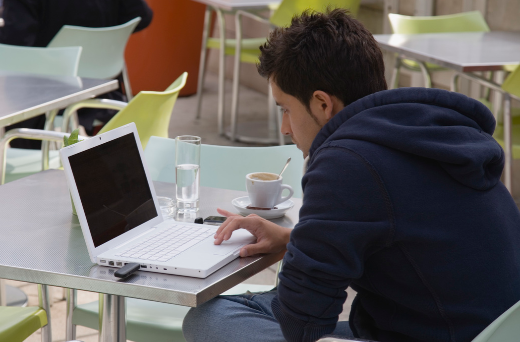 Young man having coffee while surfing the net on laptop at the Museum of Modern Art Museum