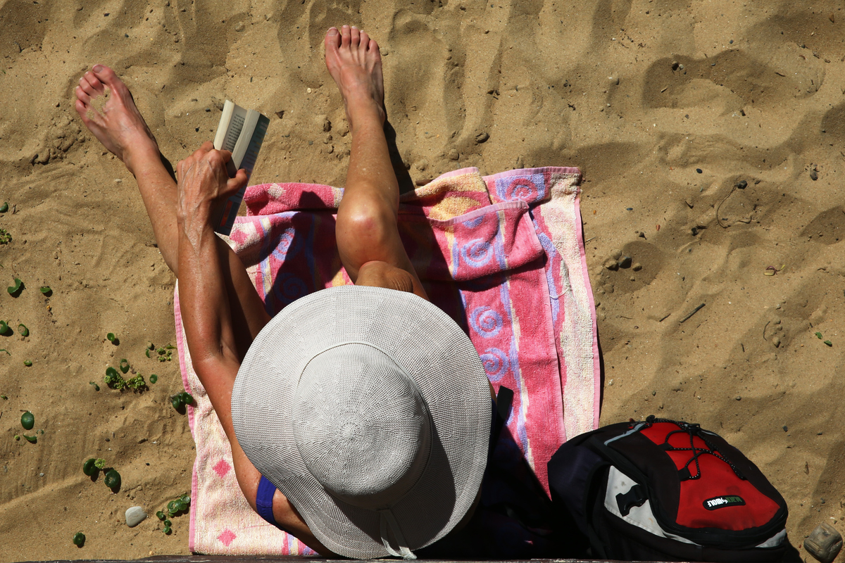Sunbather sits and reads on the beach in summer in Sydney, Australia.