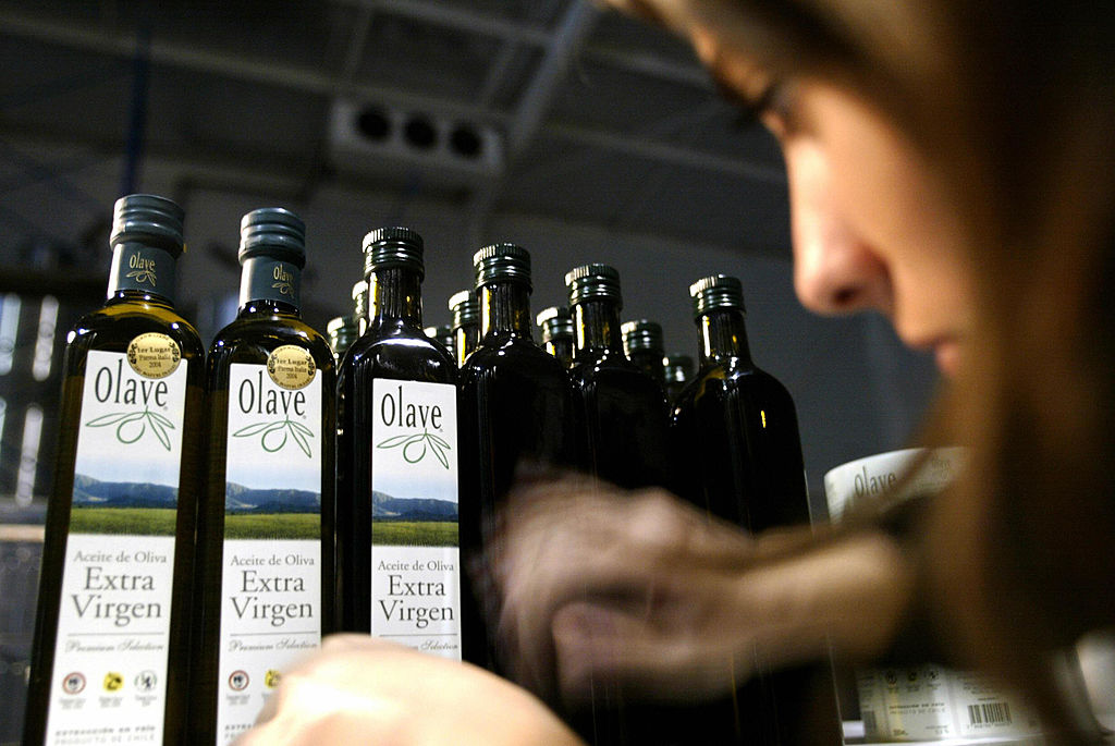 GettyImages-52909066 A woman glues labels on olive oil bottles in Melipilla of the Cholqui valley,
