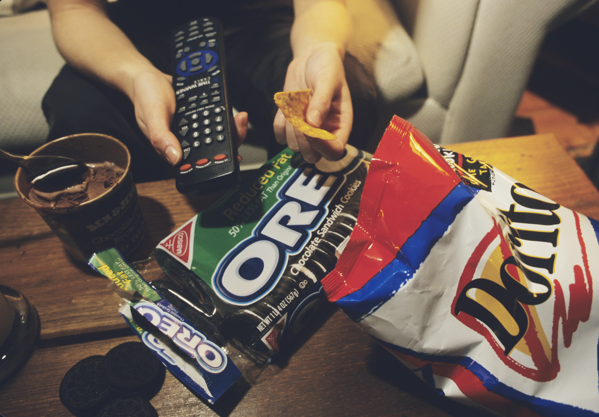 With remote control in one hand and nacho chip in the other, a teenager eats the food she likes in front of the TV.