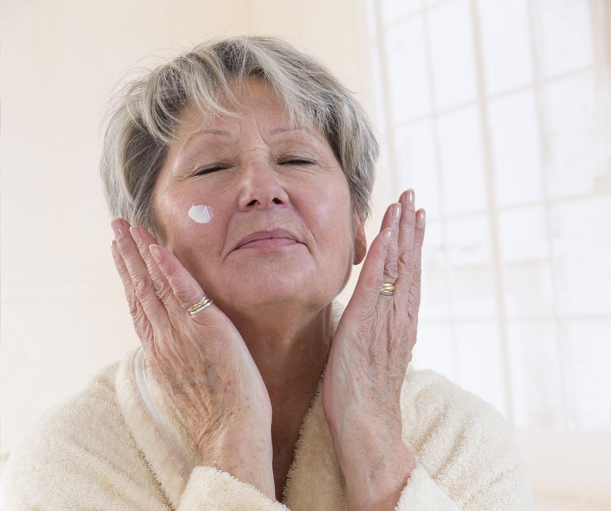 Senior woman rubbing in face cream