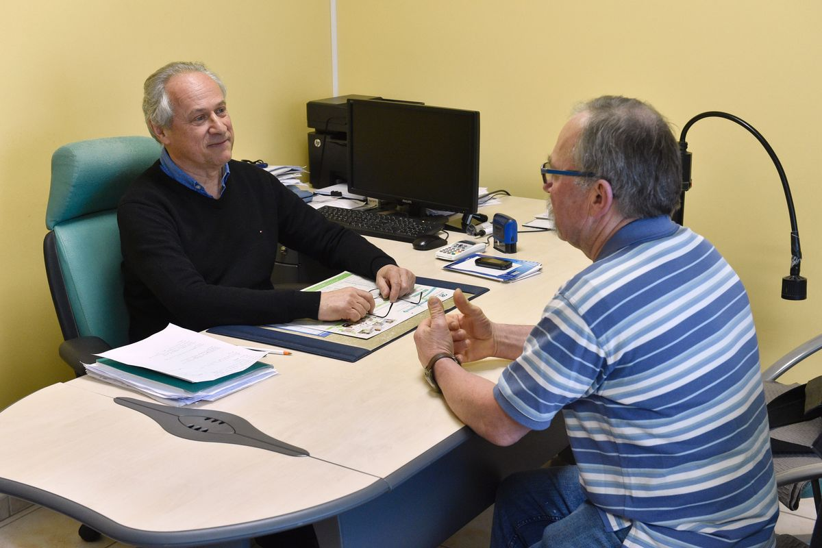 Doctor and ostheopath Pascal Gleitz speaks with a patient in his office