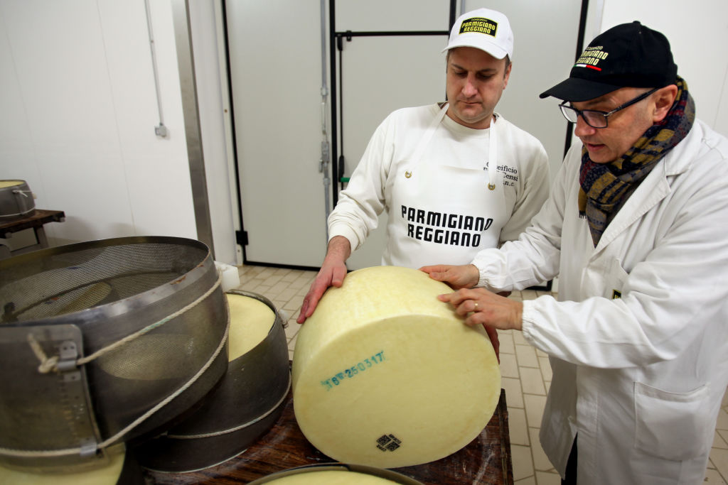GettyImages-813765144 people making a wheel of parmesan cheese