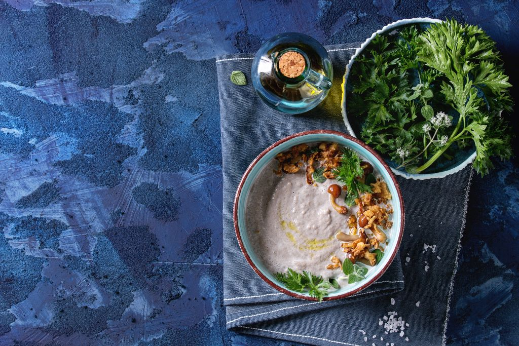 GettyImages-957722262 Mushroom cream soup in ceramic bowl served with forest mushrooms, greens, fried onion, salt, bottle of olive oil on blue textile napkin over dark blue texture concrete background