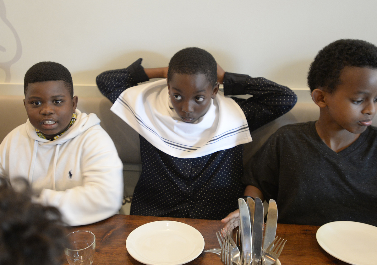 Boy places a napkin around his neck after sitting for dinner at Chaval