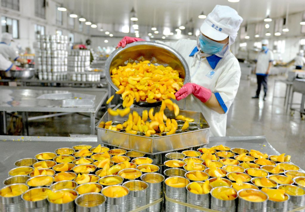 GettyImages-994405048 This photo taken on July 8, 2018 shows a worker sorting canned peaches for export at a factory in Xiayi in China's central Henan province