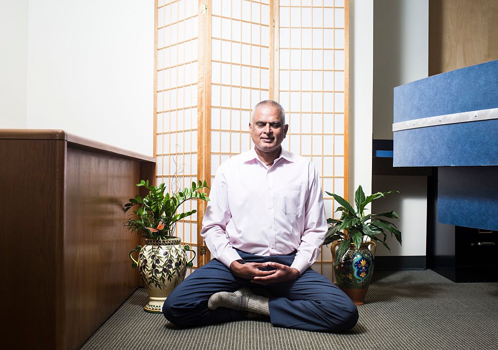 Ashok Nalamalapu meditating at his offic