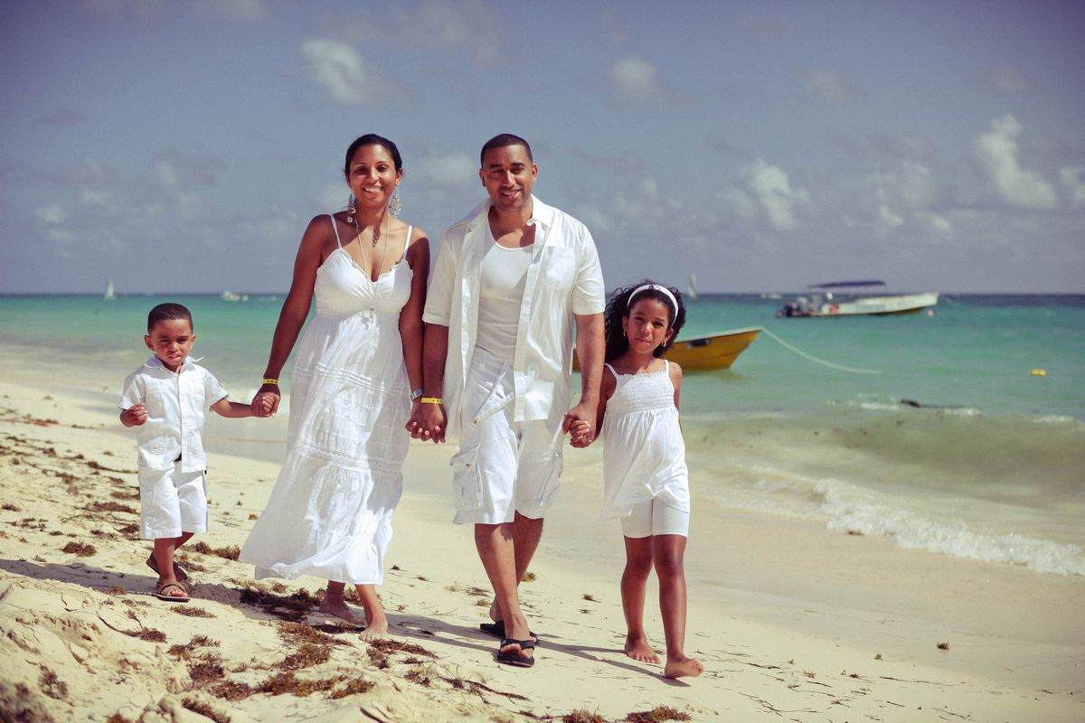 Portrait of family on the beach wearing white