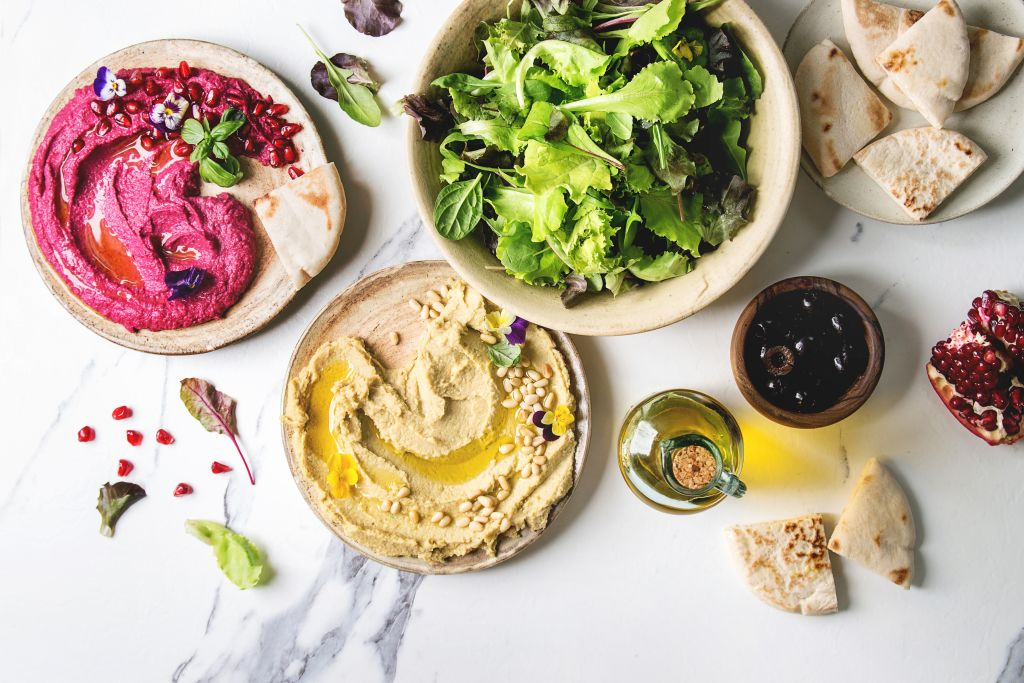 a couple varieties of hummus with pine nuts, olive oil, and pomegranite with pita bread