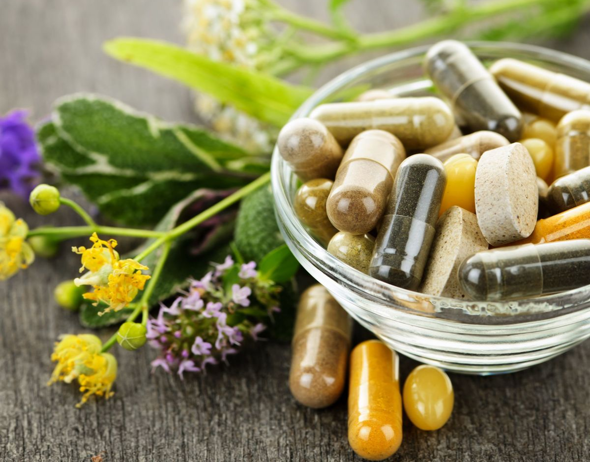jar of herbal supplements next to fresh herbs