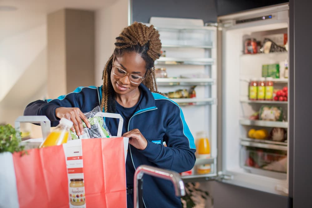 woman putting away groceries into her refrigerator