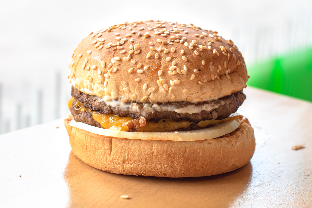 Real serving of an A&W hamburger over a wood table surface.