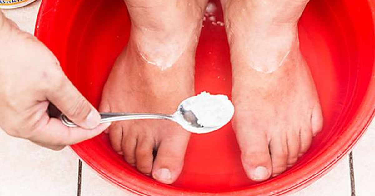 a hand holding a spoon with baking soda over a bucket with water and feet