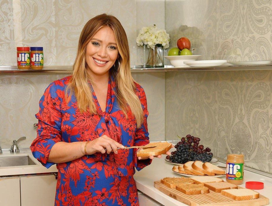 Actress Hillary Duff smiles while spreading peanut butter onto a slice of bread.