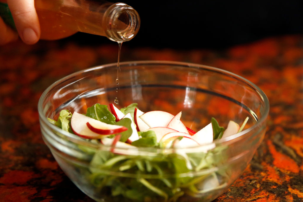 Dressing is poured from a bottle over a small salad.