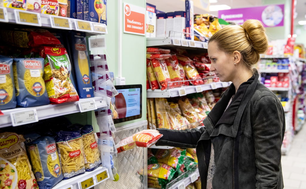A woman holds a bag of dried pasta in one hand while contemplating the other pastas on the shelf at a grocery store.