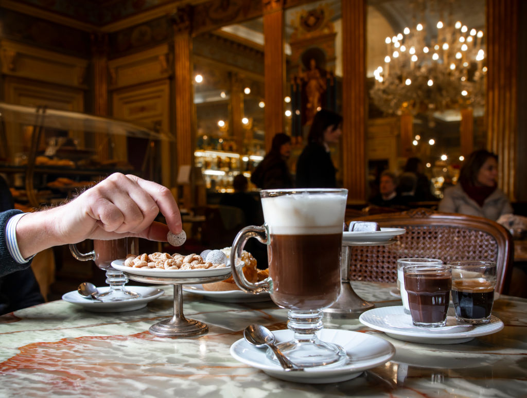 A diner enjoys hot chocolate in an elegant restaurant.