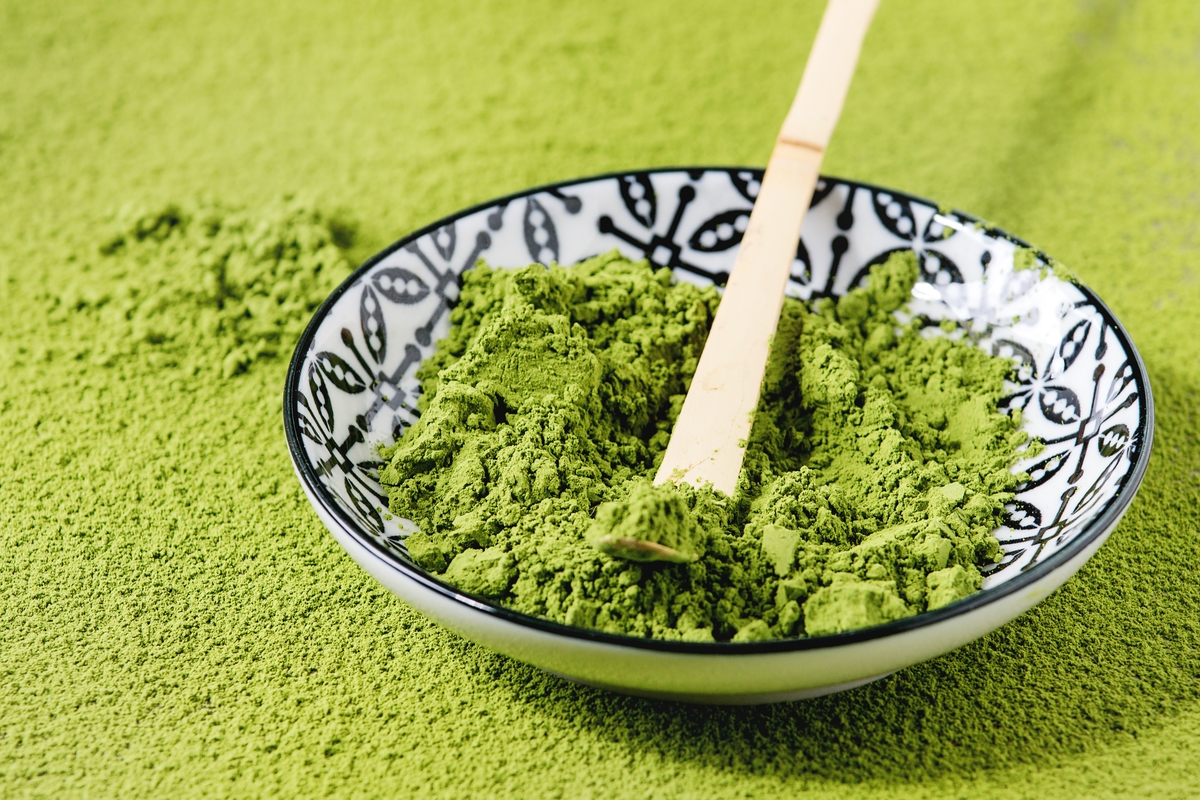 Green tea matcha powder in ceramic bowl with traditional bamboo spoon