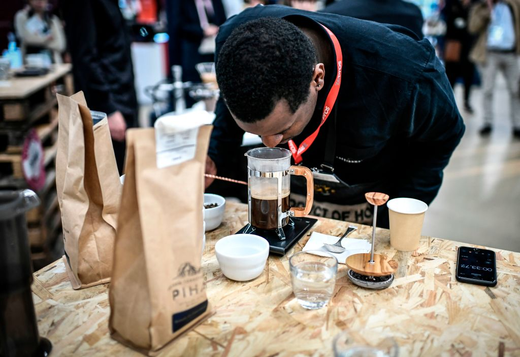 A man leans down to smell coffee brewing in a french press.