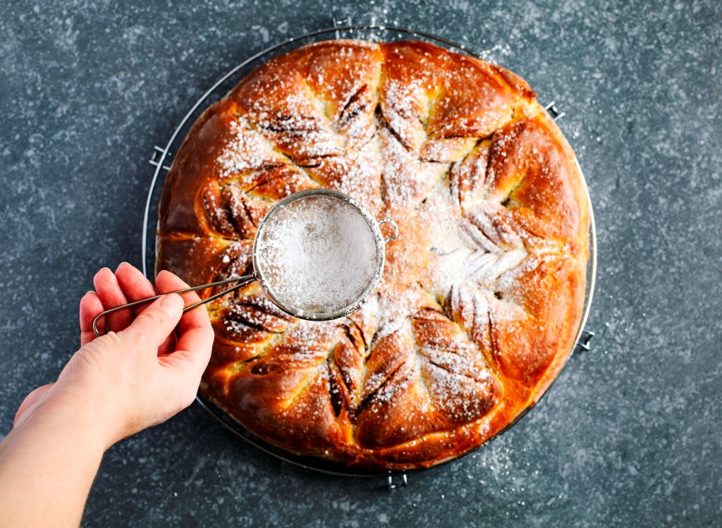 Powdered sugar is dusted over a large brioche.