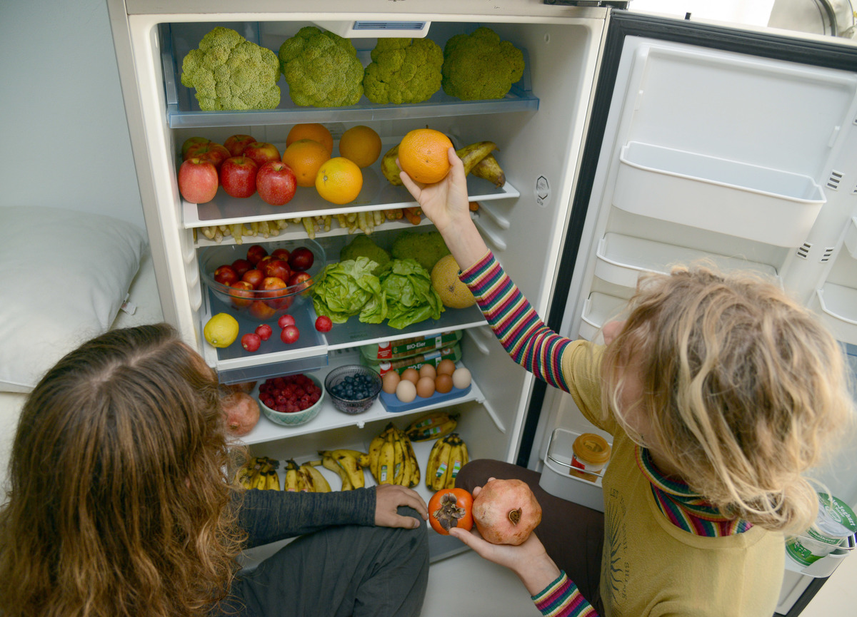 two girls picking out veg from fridge