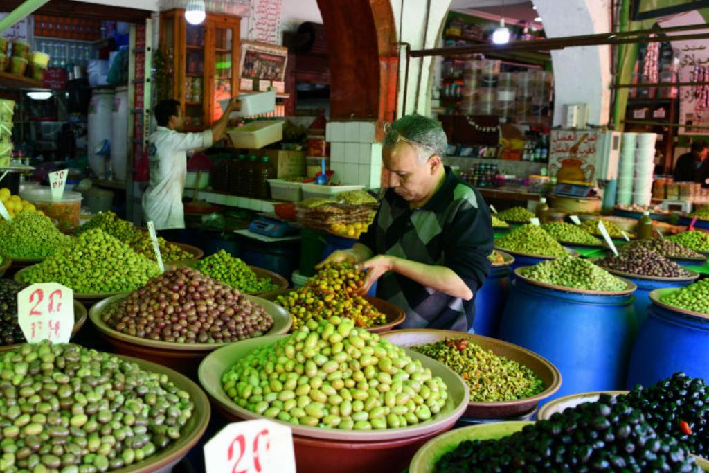 A man digs into one of several olive displays, each barrel holding a different variation of olives.