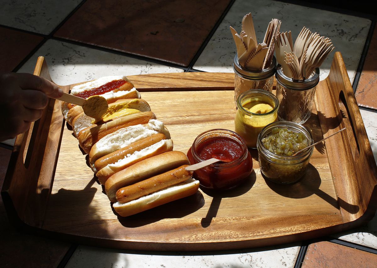 The author spreads hot mustard on a hot dogs along with homemade ketchup and zucchini-and-green pepper relish.