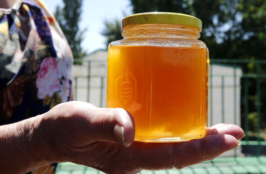A jar of honey is held in someone's palm.