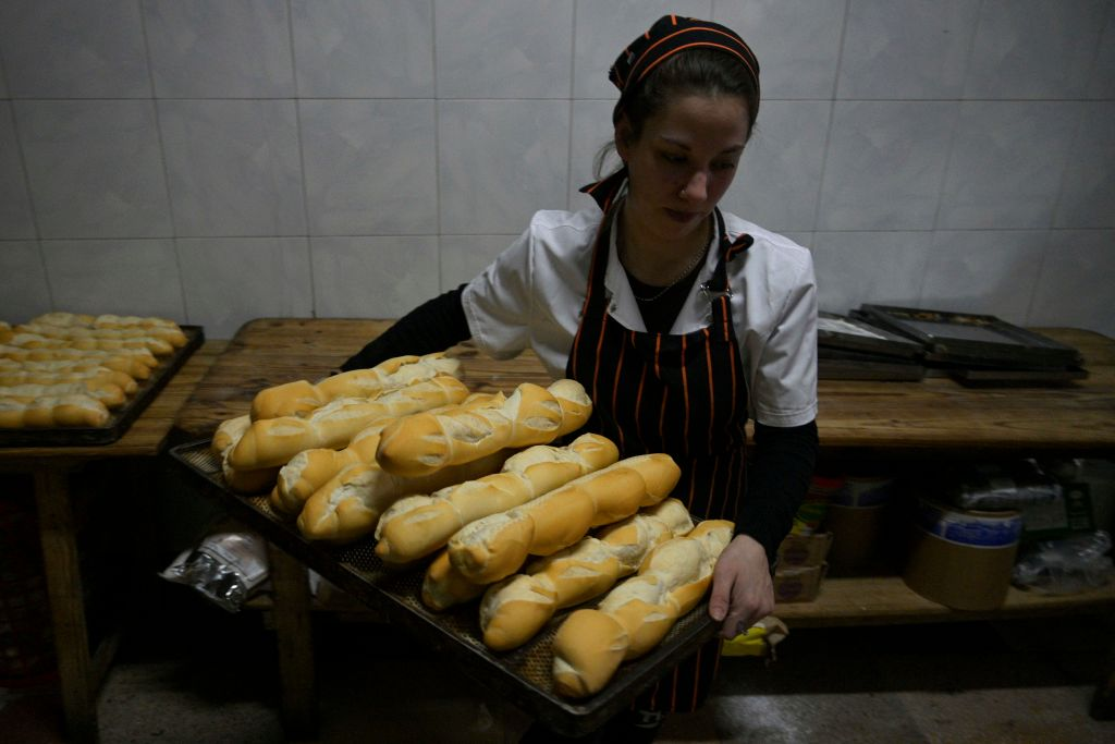 A woman carries a tray of freshly baked french rolls.