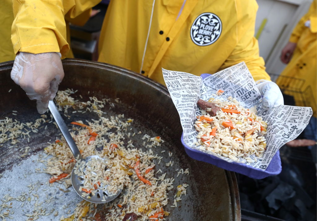 A person scoops a cooked rice dish with a ladle.