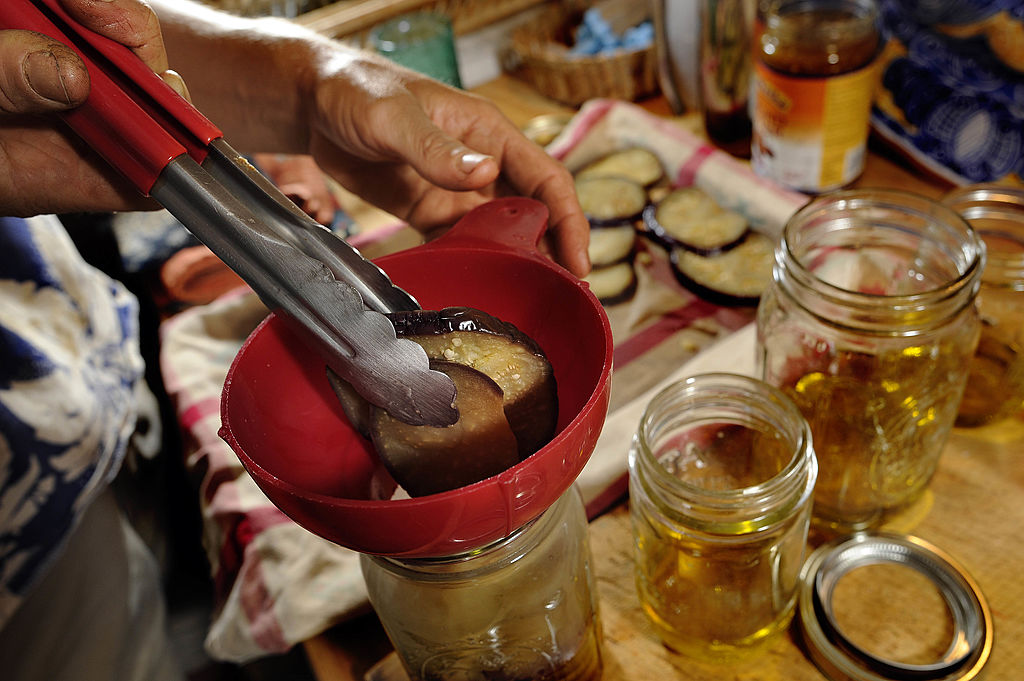 Someone uses tongs to ease pickled eggplant into a jar.