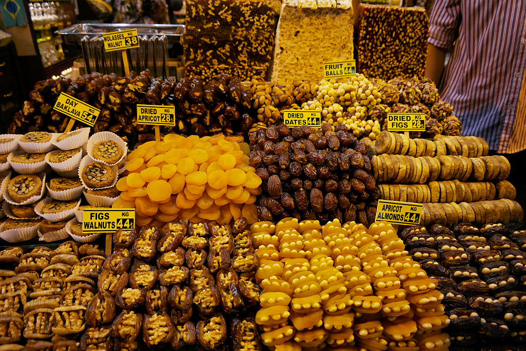 A man stands beside a dried fruit stand complete with dried out dates, apricots, and figs.