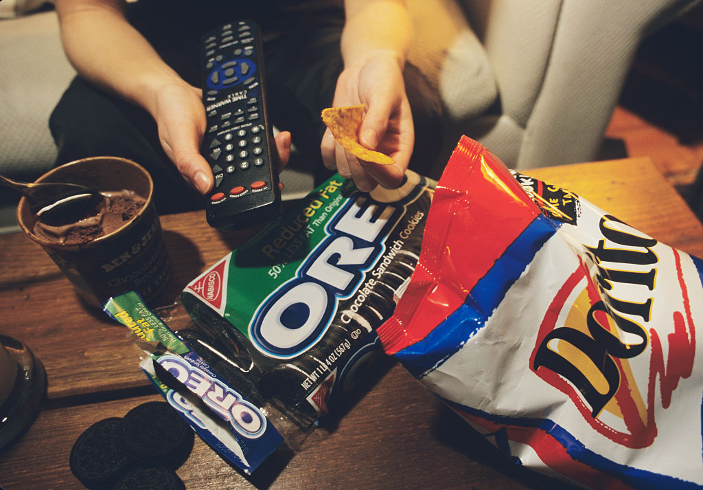 A person holds a remote in one hand and a chip in the other, surrounded by junk food.