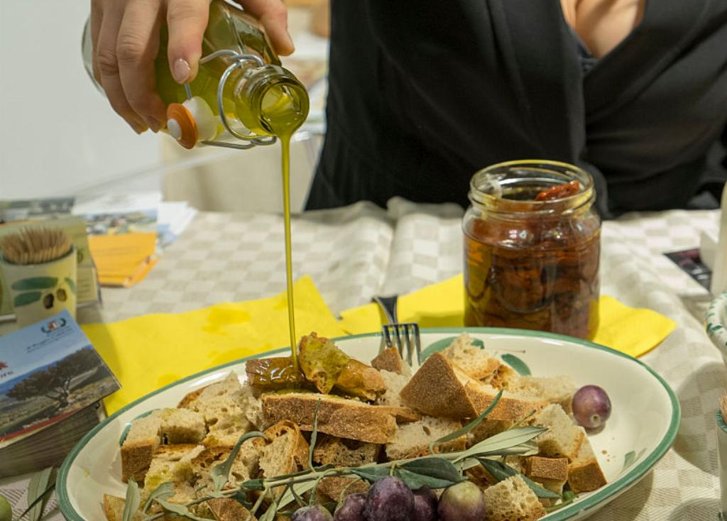 A woman pours olive oil over a plate of bread peices.