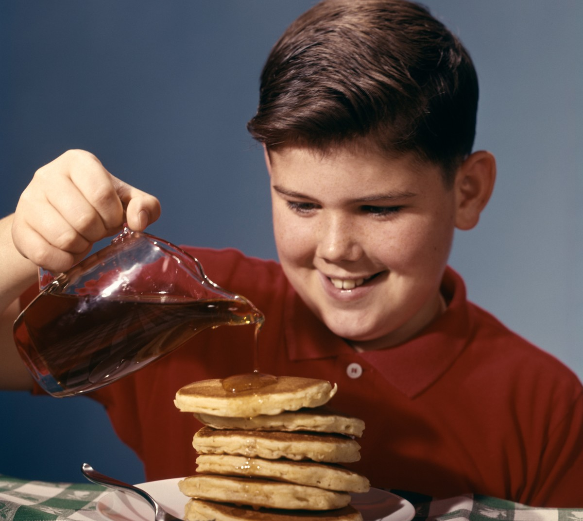 A smiling boy pours maple syrup over a tall stack of pancakes.