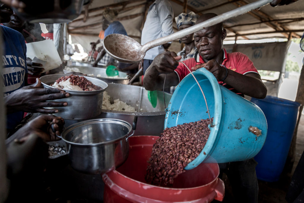 A man pours cooked beans out of a smaller bucket and into a larger one.