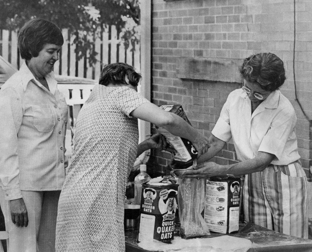 Two older women work together to pour packages of quaker oats into a clear storage bag.