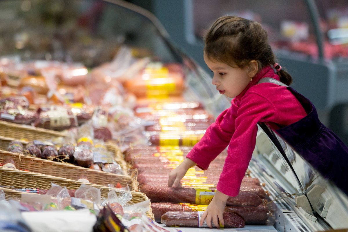 A girl reaching for salami at a Lenta supermarket in Russia