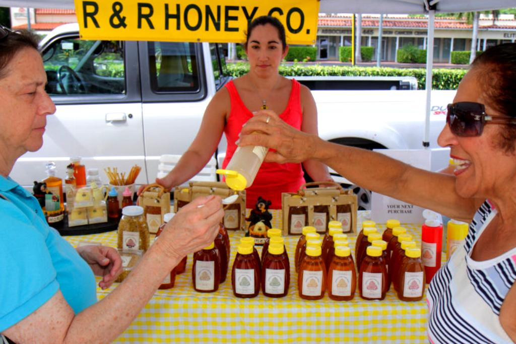 Two women happily taste honey at an outside vendor booth.
