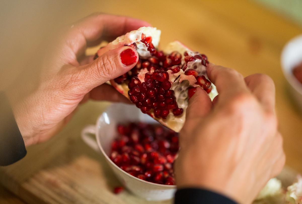 A woman pealing a pomegranade.