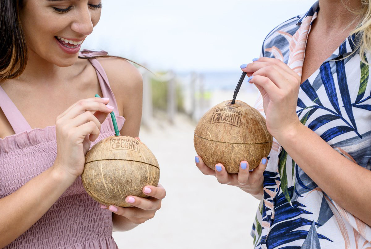 two women drinking coconut water out of coconut containers