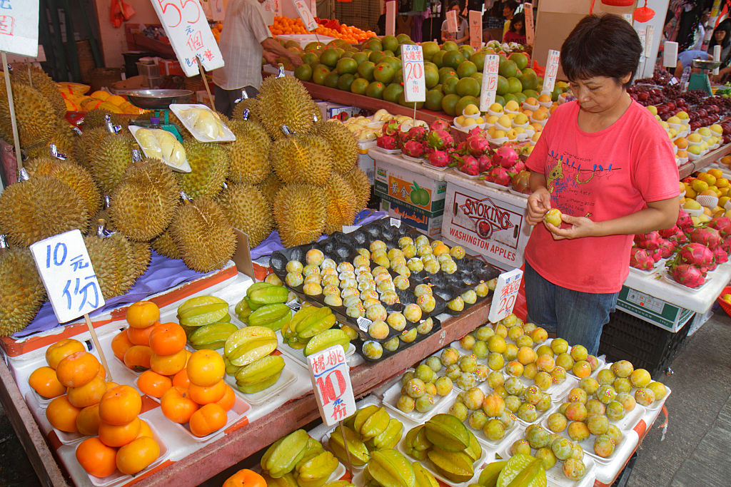 a woman looking at various types of exotic fruit at a market