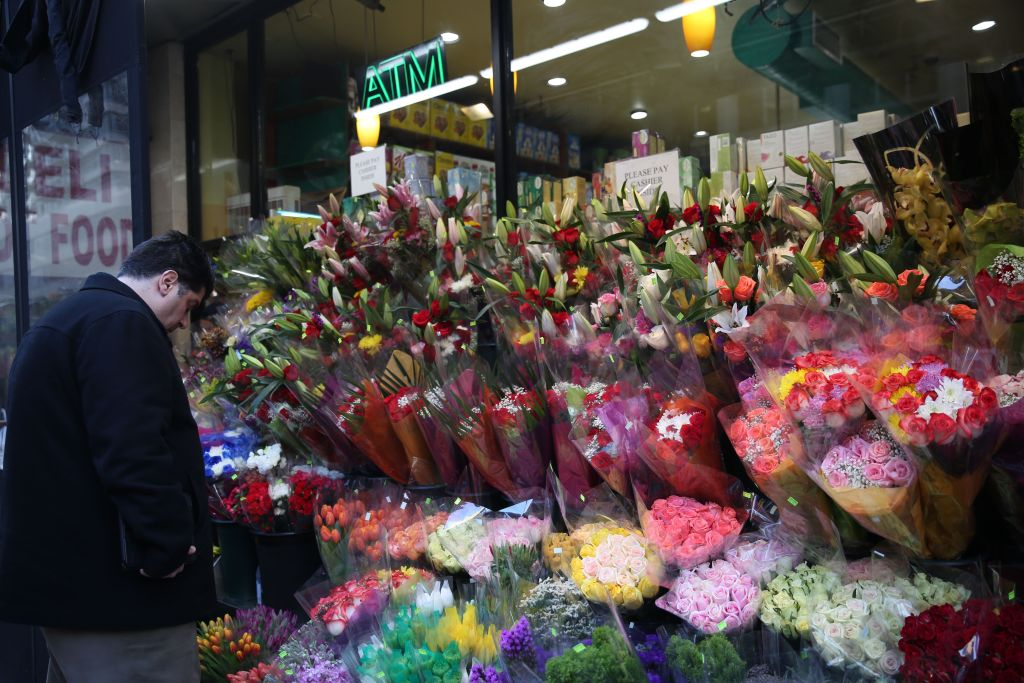 a man looking at the pre-arranged flower selection in front of a store