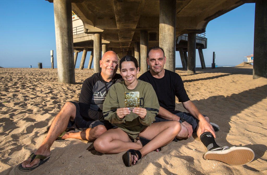two men and a teen girl sitting on a beach holding a gift card