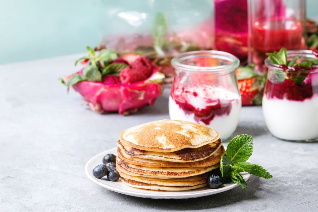 a stack of pancakes on a plate with berries, mint, and glass jars of yogurt