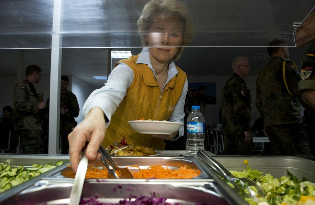 a woman putting together a salad at a salad bar