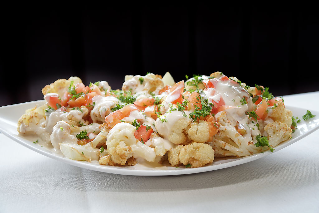 fried cauliflower drizzled with tahini sauce, parsley, and tomatoes